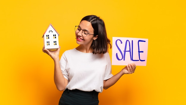 家と販売ボードを保持している若いきれいな女性