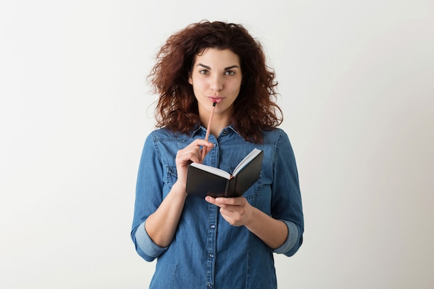 Young pretty woman holding notebook, pencil at lips, thinking, smiling, curly hair, pensive, happy, isolated