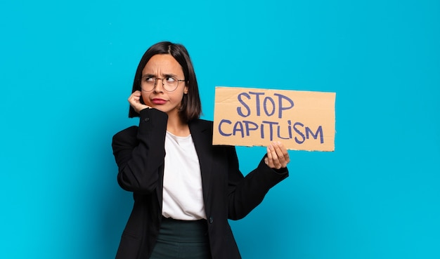 Young pretty woman holding stop capitalism board
