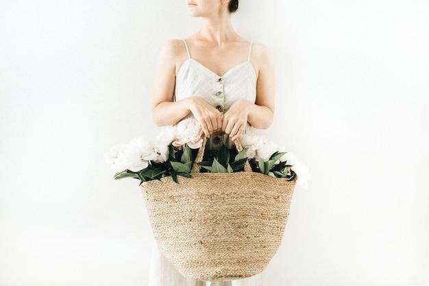 白い背景に白い牡丹の花のストロー バッグを保持している若いきれいな女性