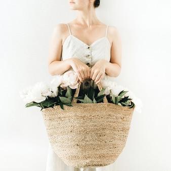 Молодая красивая женщина держит соломенный мешок с белыми цветами пиона на белой поверхности