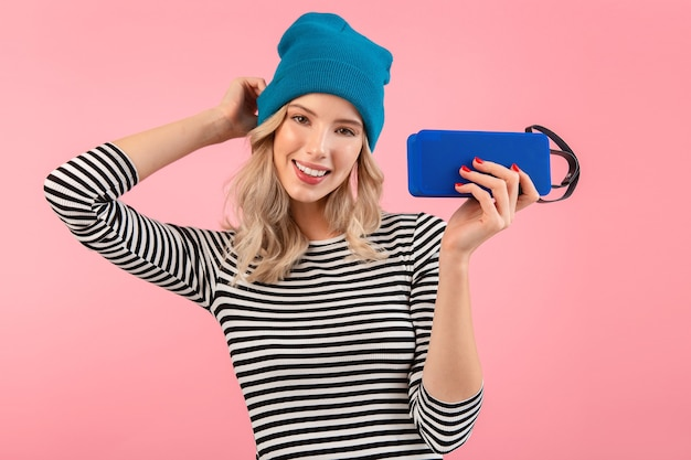 Young pretty woman holding wireless speaker listening to music wearing striped shirt and blue hat smiling happy positive mood posing on pink background isolated