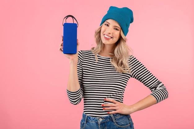Giovane bella donna con altoparlante wireless che ascolta musica indossando camicia a righe e cappello blu sorridente felice umore positivo in posa su sfondo rosa