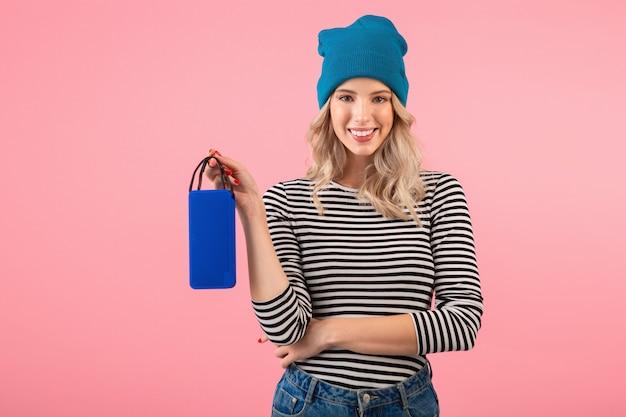 Молодая красивая женщина, держащая беспроводной динамик, слушает музыку в полосатой рубашке и синей шляпе, улыбаясь счастливым позитивным настроением, позирует на розовой стене изолированы