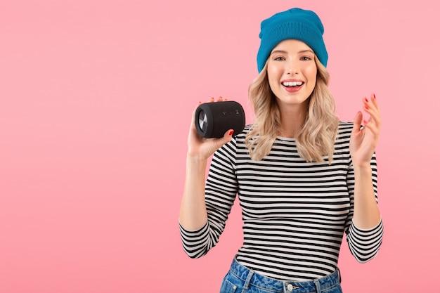 分離されたピンクの壁にポーズをとって幸せな前向きな気分を笑顔ストライプシャツと青い帽子を身に着けている音楽を聴いてワイヤレススピーカーを保持している若いきれいな女性