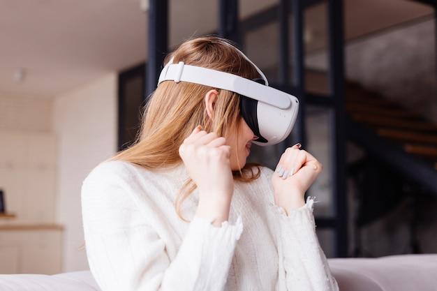 Giovane bella donna a casa che gioca a giochi vr con occhiali per realtà virtuale