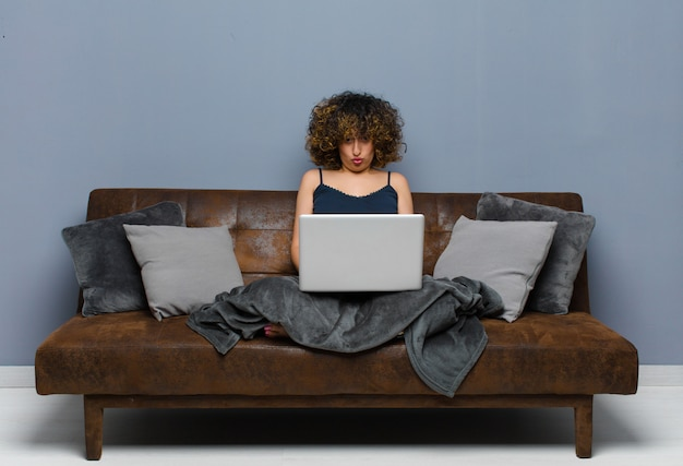 Young pretty woman at home, sitting on a sofa with a laptop