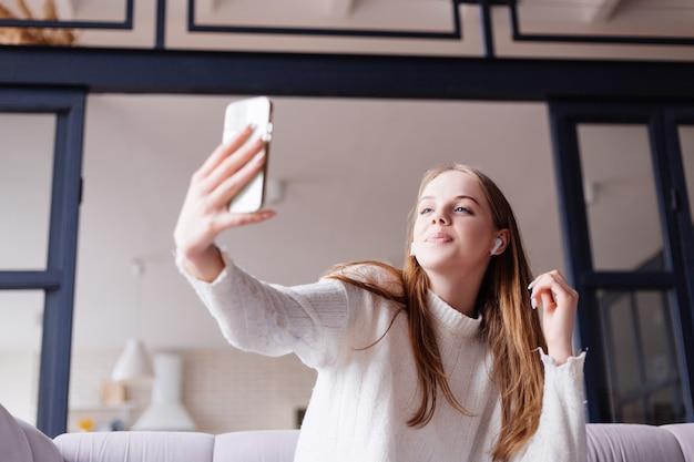 Giovane bella donna a casa sul divano che scatta foto selfie