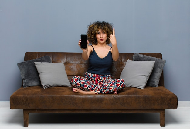 Young pretty woman at home, with a mobile phone, wearing pajamas on a sofa