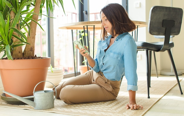Young pretty woman at home with plants