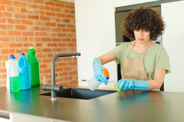 家で皿洗いをする若いきれいな女性の家政婦