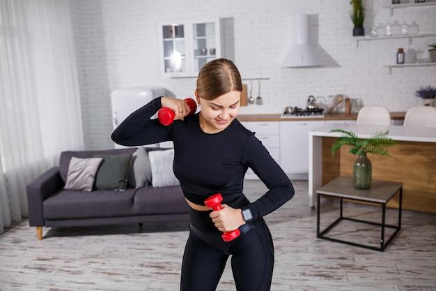 Молодая красивая женщина в черном топе с гантелями в руках занимается спортом дома, фитнесом дома во время карантина. здоровый образ жизни