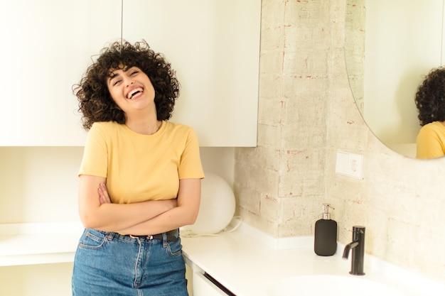 新しい家の浴室の若いきれいな女性