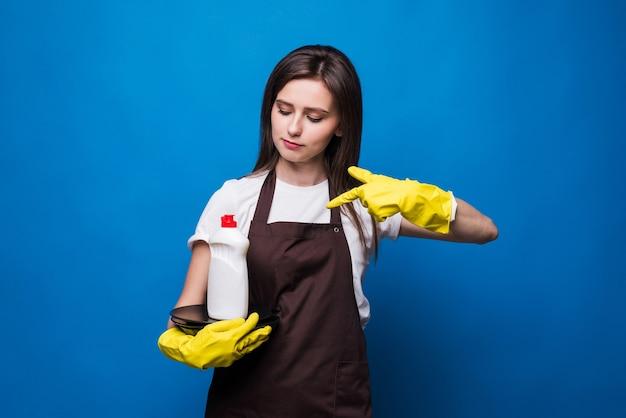 洗った皿と皿石鹸でエプロンの若いきれいな女性。きれいなプレートのスタックに空白のラベルが付いた食器用石鹸のボトル