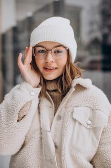 겨울 시간에 거리에서 걷고 베이지 색 옷에 젊은 예쁜 여자