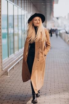 Молодая красивая женщина в черной шляпе и бежевом пальто гуляет по торговому центру