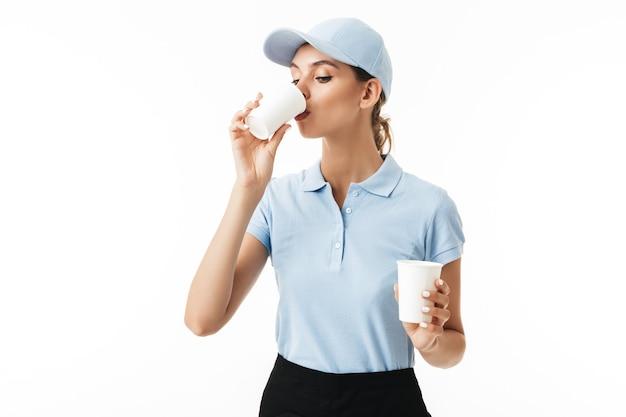 Молодая красивая женщина в синей футболке-поло и кепке пьет из одноразовой чашки