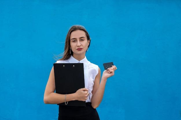 비즈니스 천을 입은 젊은 예쁜 여성이 파란색 배경에 자동차 키를 들고 있습니다.