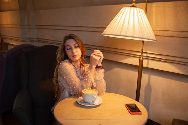 カフェで若いきれいな女性。ベージュのブラウスを着たカフェの女の子。黒のショートパンツと長い巻き毛のベージュのブラウスでコーヒーショップの若い女の子。女の子はカフェでコーヒーを飲みます。ラテ、カプチーノ