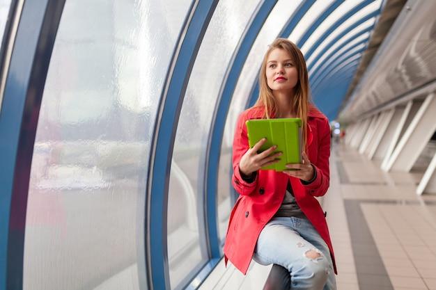Молодая красивая женщина в повседневной одежде держит планшетный ноутбук в городском здании, в джинсах, розовом тренче, у окна с видом на город, онлайн-образование