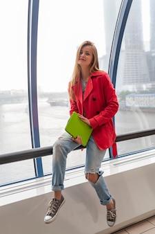 街の景色を望む窓に座っているジーンズ、ピンクのトレンチジャケットを着て、都市の建物でタブレットラップトップを保持しているカジュアルな服装の若いきれいな女性