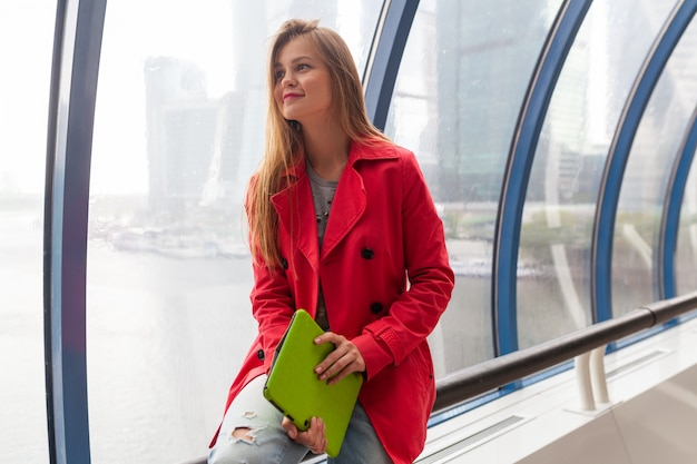Молодая красивая женщина в повседневной одежде, держащая планшетный ноутбук в городском здании, в джинсах, розовом плаще, сидит у окна с видом на город