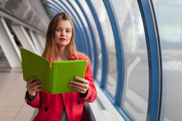 Молодая красивая женщина в повседневной одежде, держащая планшетный ноутбук в городском здании