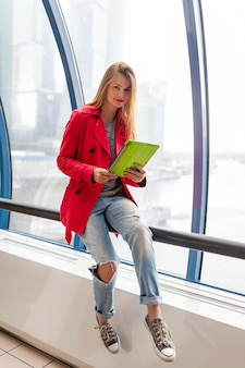 都市の建物でタブレットラップトップを保持しているカジュアルな服装の若いきれいな女性