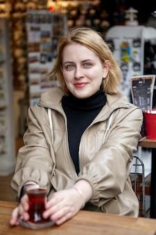 カジュアルなレインコートを着た若いきれいな女性が彼女の手にトルコのお茶の小さなカップを持って外のカフェに座っています