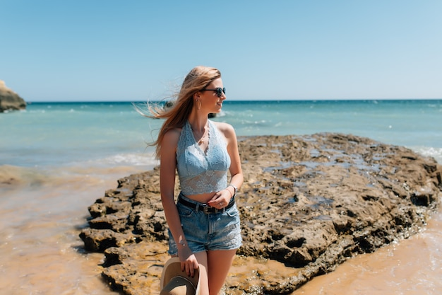 ビーチの帽子の若いきれいな女性