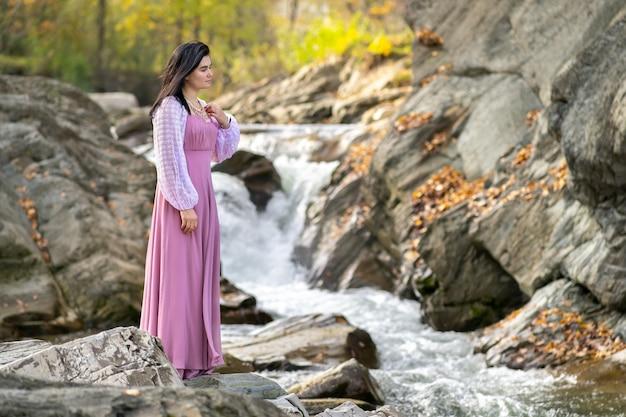 Молодая красивая женщина в длинном розовом модном платье стоит возле речки с быстро движущейся водой.