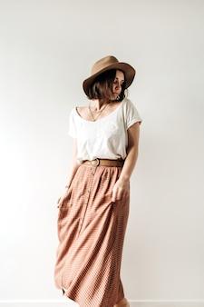 長いスカート、帽子、白の白いブラウスの若いきれいな女性