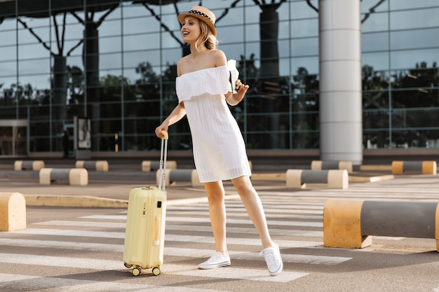 Молодая симпатичная женщина в большом белом платье смотрит вдаль, держит желтый чемодан и паспорт