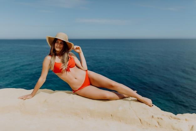 海の景色を望む石の丘の上に横たわっている赤いビキニと麦わら帽子の若いきれいな女性
