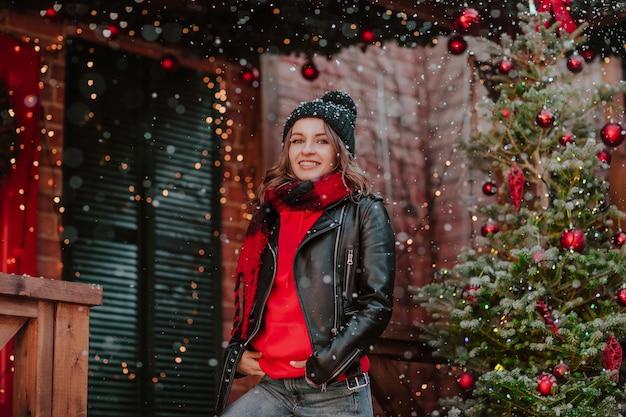 赤い冬のパーカー、黒い革のジャケット、帽子、ジーンズのポーズで若いきれいな女性