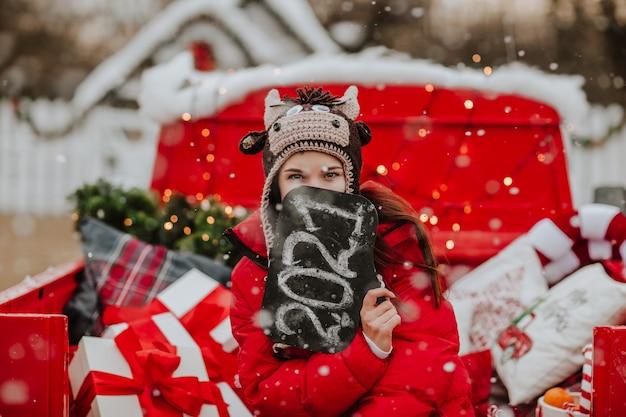 Молодая симпатичная женщина в красной зимней куртке и вязаной шапке, как бык, позирует с табличкой 2021 года в открытой красной машине с рождественским декором. идет снег.