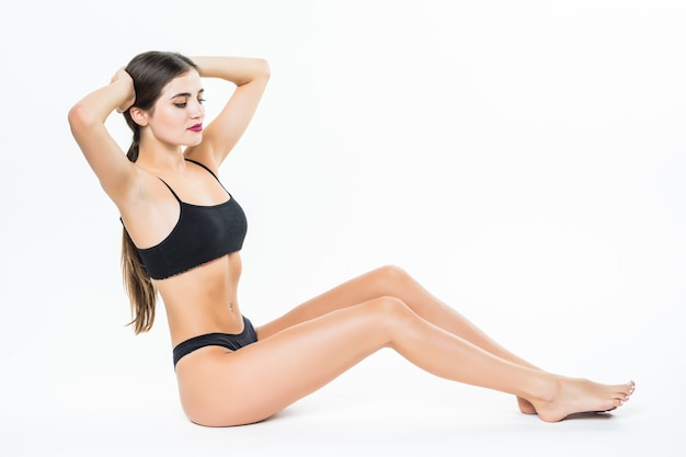 Молодая красивая женщина в спортивной одежде, сидя на полу у себя дома