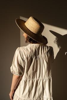 밀 짚 모자와 흰색 드레스 sundress에 젊은 예쁜 여자. 벽에 햇빛 그림자