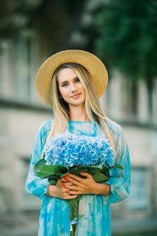 밀짚모자를 쓴 젊고 예쁜 여자가 여름 거리에서 수국과 함께 웃고 있다