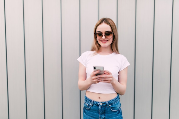 サングラスの若いきれいな女性は、屋外の縞模様の壁に立っている携帯電話を使用します。