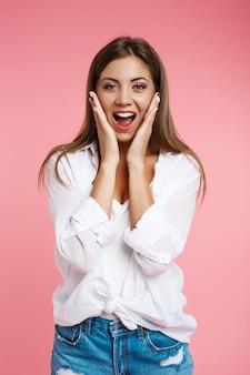 Молодая красивая женщина в тредном наряде выглядит счастливой и удивленной