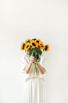 白いドレスを着た若いきれいな女性は白にひまわりの花束を保持します。