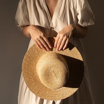 밀 짚 모자를 들고 흰 드레스 sundress에 젊은 예쁜 여자. 최소한의 패션 디자인 컨셉