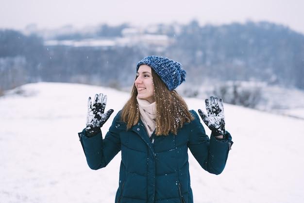 Молодая красивая женщина в зимней одежде и перчатках с улыбкой снега.