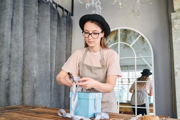 Молодая красивая женщина в спецодежде и шляпе резки ленты заканчивается на верхней части подарочной коробки, стоя за столом в студии