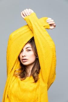 灰色の壁に分離された上げられた手で黄色いセーターの若いきれいな女性