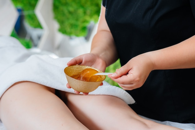 A young pretty woman is enjoying a professional massage using honey at the spa