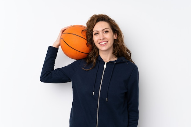 Young pretty woman over isolated with ball of basketball