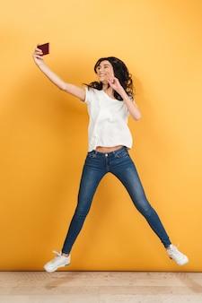 ジャンプ若いきれいな女性は、平和のジェスチャーで電話でselfieを作ります。