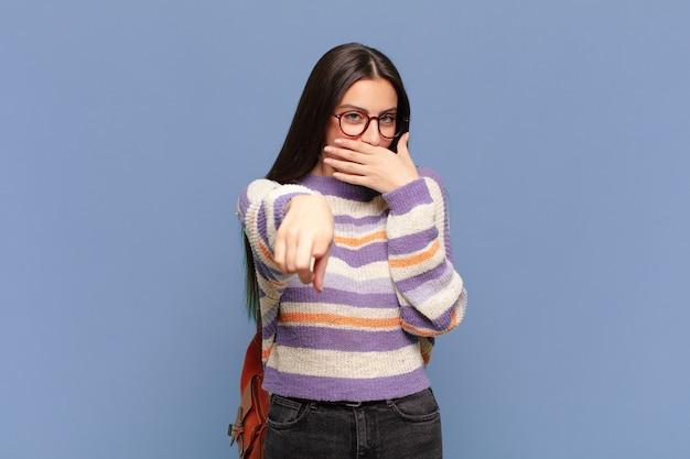 あなたを笑い、カメラを指して、あなたをからかったり、あざけったりする若いきれいな女性。学生の概念